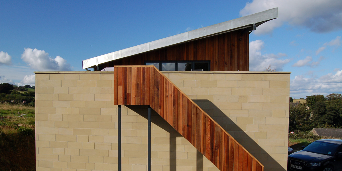 Cedar cladding, sandstone and grey window frames work well as a palate of colours and textures